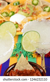 Cinco de Mayo Concept: Margaritas and Mexican food on a colorful  table cloth, with nachos and salsa.