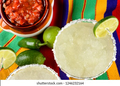 Cinco de Mayo Concept: Margaritas and Salsa on a colorful  table cloth, with limes, and peppers.