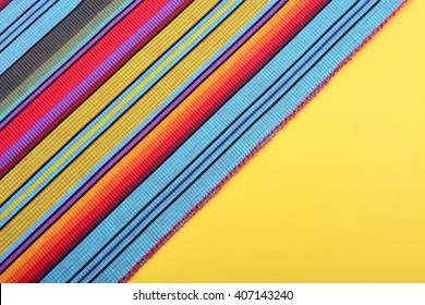 Cinco de Mayo festive stripe material on yellow background, with copy space.