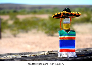 Cinco de Mayo, the fifth of May, is a holiday celebration involving the date of the Mexican army's 1862 victory over France` Beer bottle wearing poncho and sombrero.
