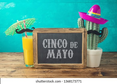 Cinco de Mayo holiday background with chalkboard, Mexican cactus, party sombrero hat and orange juice on wooden table