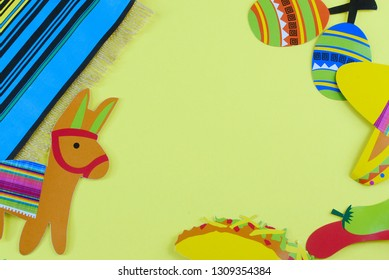 Cinco de Mayo image with copy space on yellow background surrounded by colorful party props with Mexican themed subjects
