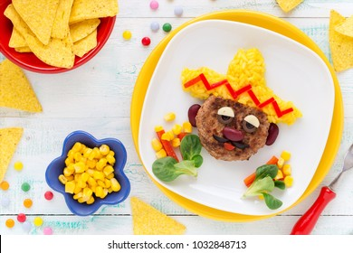Cinco de Mayo Mexican fun food for kids - very cute face on a meat hamburger or ground meat pattie with yellow rice sombrero decorated with bell peper, swwt corn and salad. Overhear view