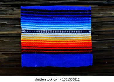 Cinco de Mayo poncho blanket on dark wood background.