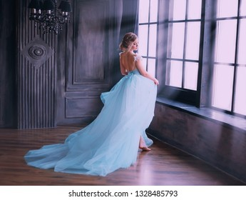 Cinderella after the fabulous incarnation, happy runs up to the window. The room is filled with magical rays of moonlight. Gothic dark room of the castle in vintage style. Fine Art photography