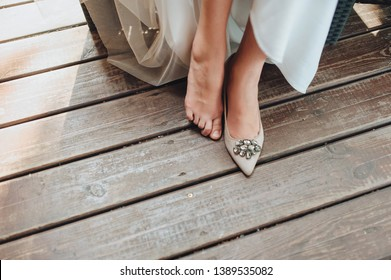 Cinderella. The bride sits in one shoe with one foot without shoes against the background of a wooden parquet. Wedding ceremony and tradition in Ukraine, Russia. Abduction shoes. Barefoot bride.