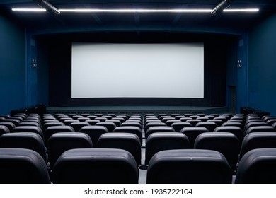 Cinema auditorium with black seats and white blank screen. Concept of interior cinema hall and preparing for new visitors.