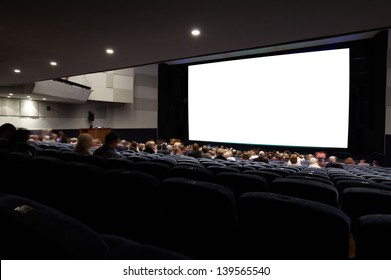 Cinema auditorium with people in chairs watching movie. Ready for adding your own picture. Diagonal perspective view.