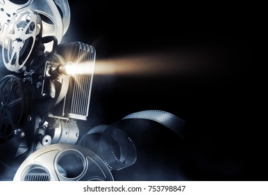 Cinema background with movie projector and film reels on a dark background / high contrast image