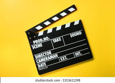 Cinema clapperboard on color background