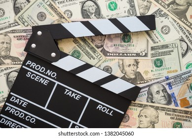 Cinema clapperboard on US dollars banknote bill background - Movie entertainment industry to make money concept