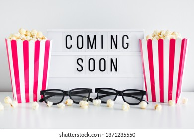 """cinema concept - red striped boxes with popcorn, 3d glasses and light box with """"coming soon"""" text"""