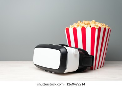 Cinema concept of VR device, snacks in paper cup on white board on blue background