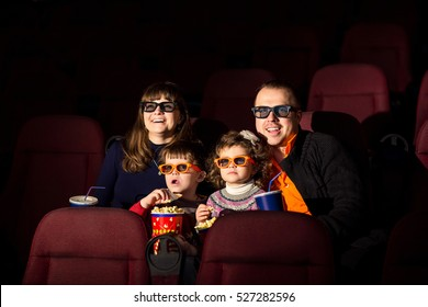 Cinema day, happy family with popcorn and drinks looking interesting film in cinema