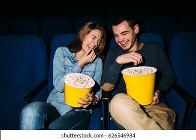 Cinema day. Happy young couple watching comedy movie in cinema, smiling.