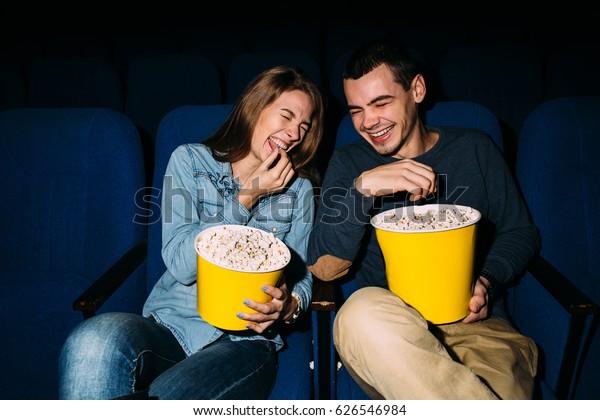 映画の日。喜びの若い夫婦は、映画でコメディ映画を見て、微笑みながら。