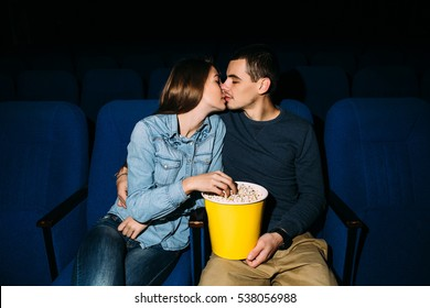 Cinema day. Young beautiful couple kissing while watching romantic movie at cinema. Romantic date in cinema.