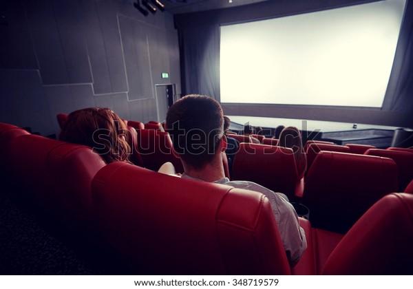 concepto de cine, entretenimiento, ocio y personas: parejas viendo películas desde atrás