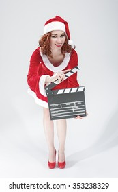 Cinema and Film Production Concept and Ideas. Full Length Portrait Of Smiling Female Santa Girl with Clapperboard Posing Against  White Background.Vertical Shot