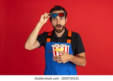 At cinema. Funny young bearded man, male auto mechanic or fitter wearing blue work dungarees isolated over red studio background. Concept of funny meme emotions, ad, job, insipation, ideas, sales