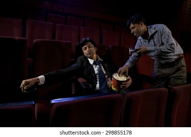 Cinema hall attendant taking popcorn from a sleeping man