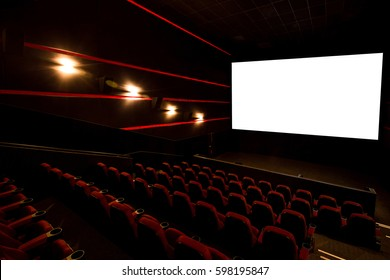 Cinema hall, white screen with copy space and empty armchairs. Movie theatre