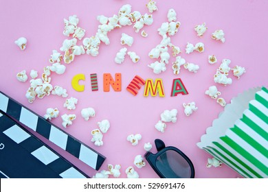 cinema letters, 3d glasses, clapper board and pop corn.Flat lay