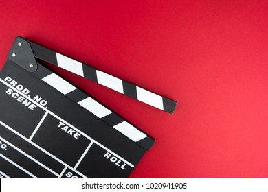 Cinema minimal concept. Watching film in the cinema. clapper board on red background. Screenwrite desktop