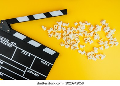 Cinema minimal concept. Watching film in the cinema. popcorn, clapper board on yellow background