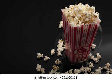 Cinema and movies concept with a box of popcorn and cinematography celluloid filmstrip rolling wround it with copy space