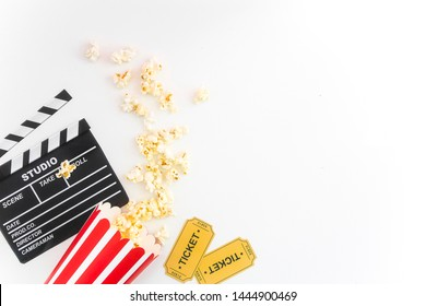 Cinema party concept. movie tickets, clapperboard, pop corn and 3d glasses in a white background. Flat lay