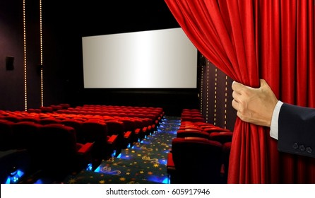 Cinema seats and blank screen with hand opening red curtain