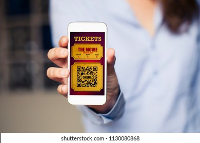 Cinema tickets in a mobile phone screen while woman holds it.
