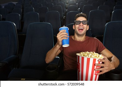 Cinema weekend. Young handsome male spectator wearing 3D glasses laughing excitedly while watching a film at the local cinema coke popcorn snack entertainment leisure hobby activity laughter copyspace