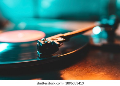 Cinemagraph loop vinyl record player turntable with its stylus running along music plate. Neon light. Retro-styled spinning record vinyl player. Close up