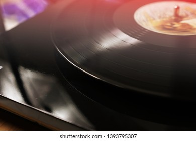 CINEMAGRAPH - seamless loop. Vinyl record is being played on a modern turntable on wooden table.