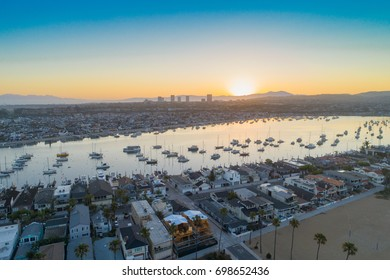 Cinematic aerial view from the drone over Balboa Peninsula in Newport Beach on a sunny morning at sunrise over Newport Beach harbor with luxury yachts, boats and mountains in view.