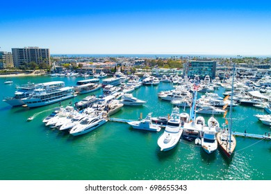 Cinematic aerial view over the Newport Beach harbor during the annual boat show with luxury yachts, boats and Duffy boats on a sunny blue sky day.
