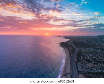 Cinematic aerial view over Pacific Coast Highway or PCH and Crystal Cove in Newport Beach fiery pink and blue skies.