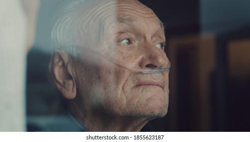 Ein kinematischer Nahaufnahme eines älteren, nachdenklichen Mannes mit Sauerstoffschlauch sieht morgens durch ein Fenster. Konzept der Gesundheitsversorgung, Leben, Rentner, Großeltern, Ruhestand, Pension.