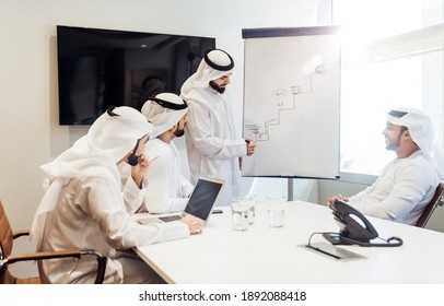 Cinematic image of an arabian group of people working in the office. Four men wearing traditional outfit from Dubai making business plans indoor