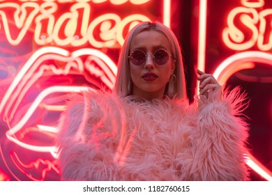 Cinematic portrait of blond girl with furry pink coat and neon sign at night