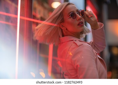 Cinematic portrait of blond girl with pink leather jacket on neon sign at night