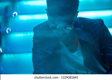 Cinematic portrait of Handsome man with sunglasses and leather jacket with cool neon lights outdoors