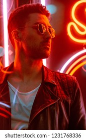 Cinematic portrait of Handsome man with sunglasses and neon ligh