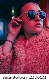 Cinematic portrait of young beautiful stylish woman blond, dressed in a white fur coat and sunglasses under neon light at night