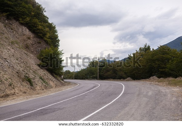 Cinematic road landscape. Asphalt Road throuth the mountains. With cloudy sky