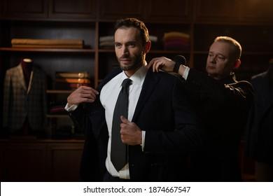 Cinematic Shot of young business man probiert seinen neuen maßgeschneiderten, hochwertigen Anzug mit Designer in Luxus-Schneideratelier.