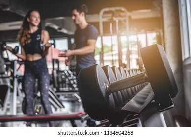 Cinematic tone of young attractive fitness woman exercise with dumbbell by trainer in gym.