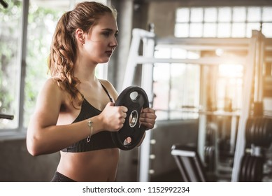 Cinematic tone of young attractive fitness woman exercise with machine in gym.